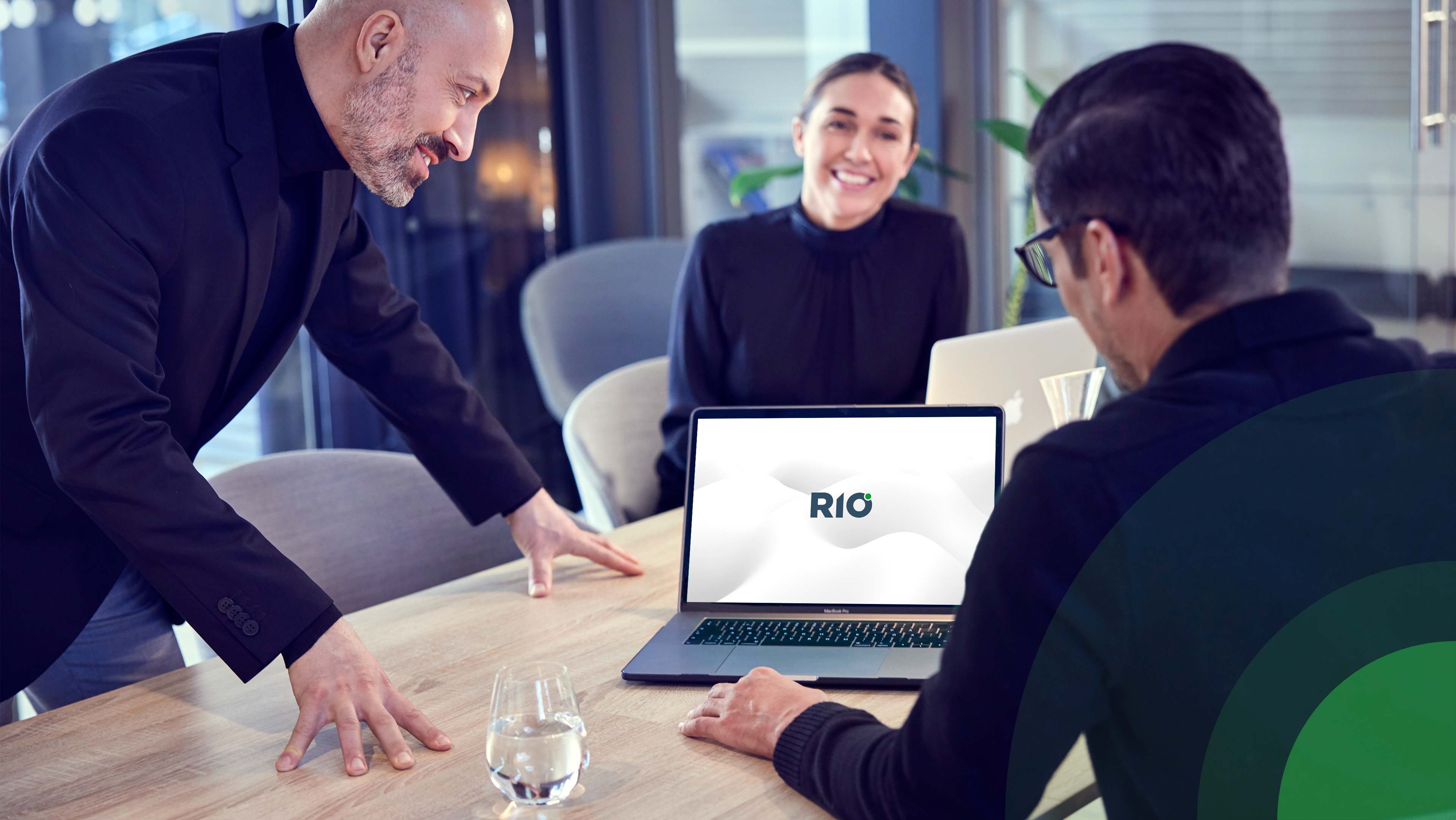 RIO team looking at a laptop with the RIO logo
